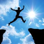 Homme sautant au dessus d'une falaise